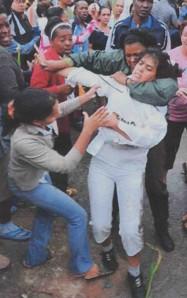 La Habana: una mujer policía inmoviliza a una joven Dama de Blanco en medio de una turba castrista que colabora en la acción represiva. Las Damas de Blanco son familiares de presos políticos y protestan caminando en silencio por las calles, vestidas de blanco y portando gladiolos.